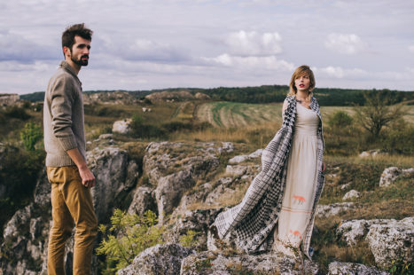 Loving couple wrapped in plaid standing on peak of mountain